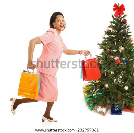 African-american female shopper running from one store to another for bargains on Christmas gifts.  Isolated on white.  - stock photo