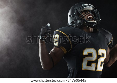 African American football player excited about winning. - stock photo