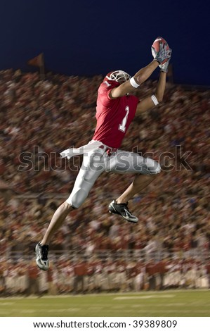 African American football wide receiver leaping up to catch a football. Vertically framed shot.