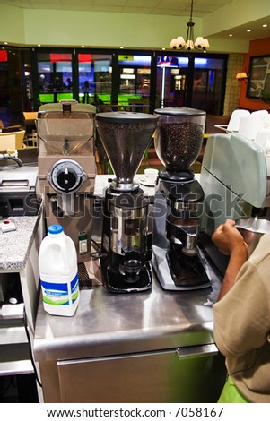 African American frothing some milk at the espresso machine in a coffee shop