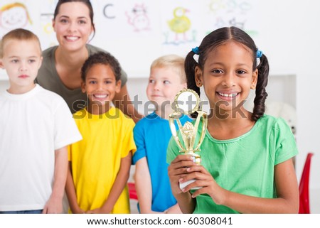 african american girl holding a trophy in front of classmates - stock photo