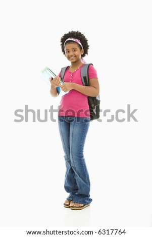 African American girl holding books and wearing backpack smiling at viewer. - stock photo