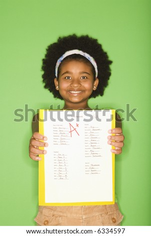 African American girl holding out graded school assignment smiling proudly at viewer.