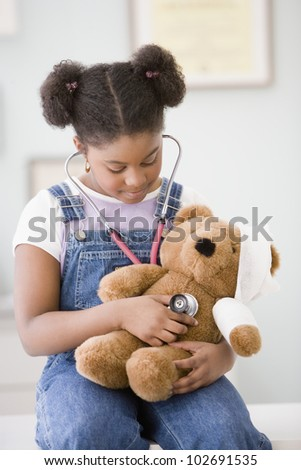 African American girl holding stethoscope on teddy bear - stock photo
