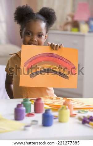 African American girl holding up painting - stock photo