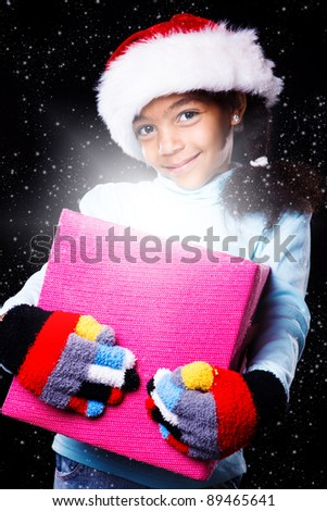 African american girl in Christmas hat holding present box, over black