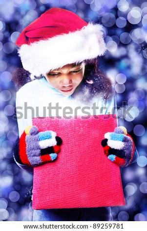 African American girl in Santa hat looking inside magic box - stock photo