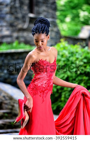 African American girl in the red dress with red shoes in her hand on the stone in the Park - stock photo