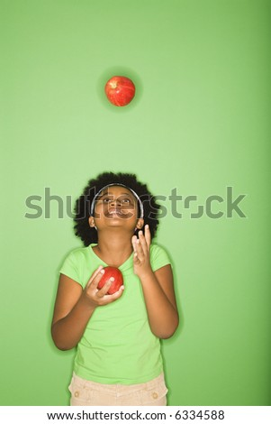 African American girl juggling apples.