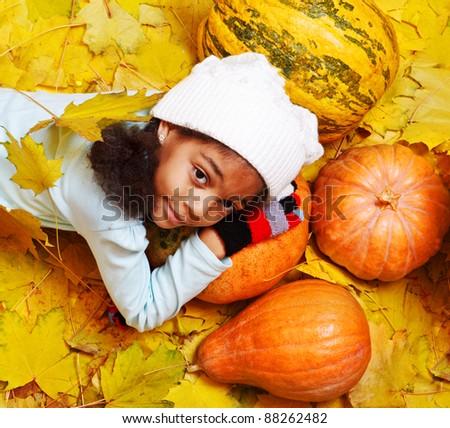 African american girl lying on pumpkin among yellow leaves - stock photo