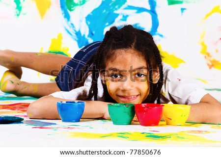 African american girl lying, plastic jars with paints beside her