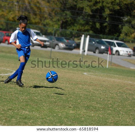 African American girl playing soccer, with focus on the ball