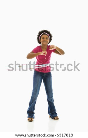 African American girl playing with hula hoop and smiling at viewer. - stock photo
