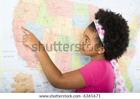 African American girl pointing on map of United States.