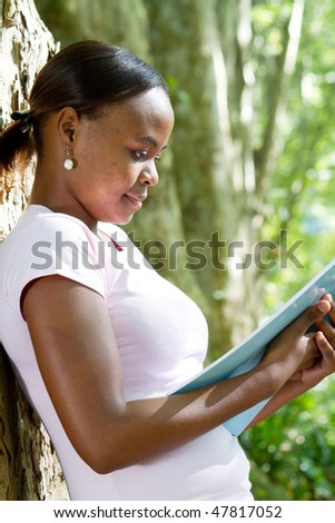 african american girl reading book in forest - stock photo