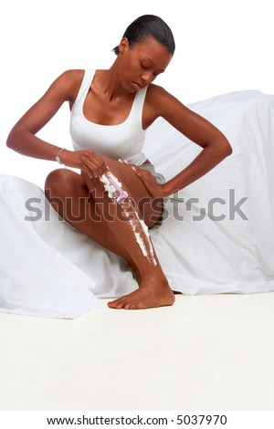 African-American girl shaves in white tank-top her legs (focus on legs) - stock photo