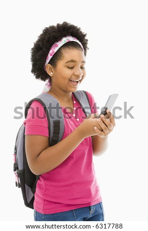 African American girl with backpack text messaging on cell phone.