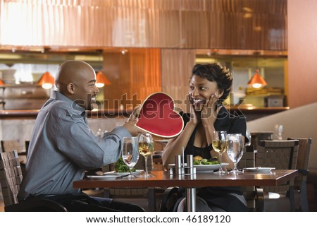 African-American gives a Valentine Day heart box to a surprised woman at a restaurant. Horizontal shot. - stock photo