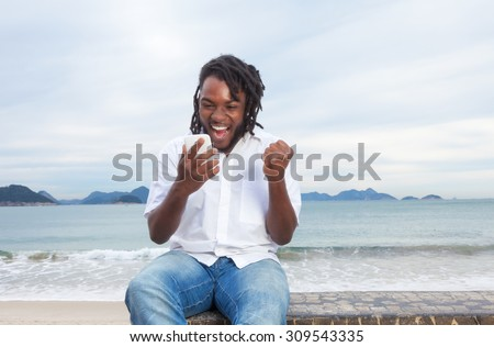 African american guy with dreadlocks and white shirt receiving good news - stock photo