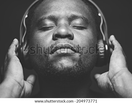 African-American guy with headphones listening to his favourite music - stock photo