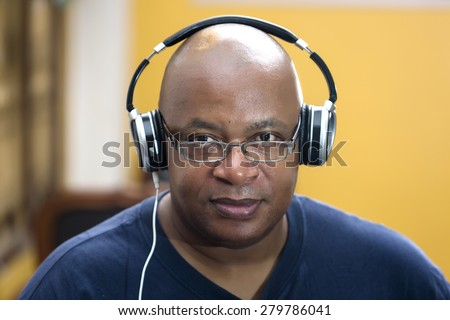 African-American guy with headphones looking at camera while listening to his favorites music - stock photo