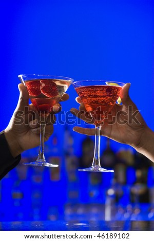 African-American hands toast martini glasses against a bright blue background. Vertical shot. - stock photo