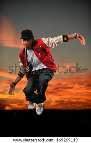 African American hip hop dancer jumping with sunset background - stock photo