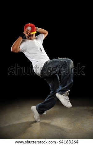 African American hip hop dancer performing over dark background