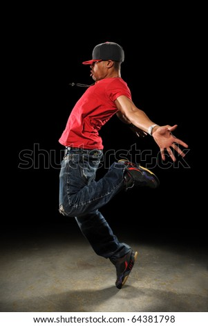 African American hip hop dancer performing over dark background with spotlight - stock photo