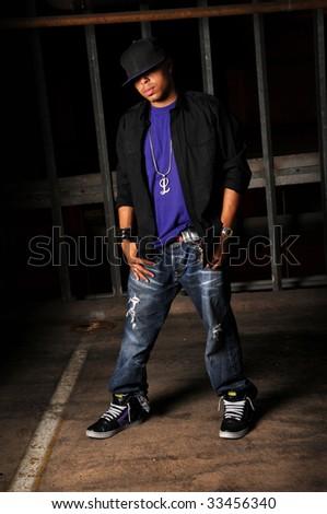 African American hip hop dancer standing over industrial background - stock photo