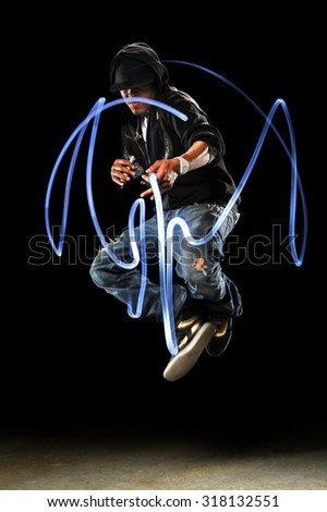 African American hip hop dancer with LED lights over dark background