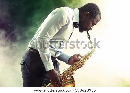 African American jazz musician playing the saxophone against smoky background - stock photo