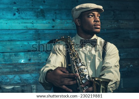 African american jazz musician with saxophone in front of old wooden wall. - stock photo