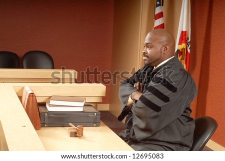 African American judge sitting in his courtroom while presiding over trial - stock photo