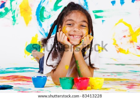 African American kid playing with finger paints
