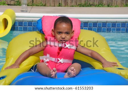 African American Latin Biracial Toddler  Sitting in Family Swimming Pool wearing Pink Life Jacket - stock photo
