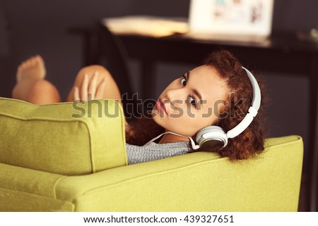 African American listening to music in headphones on green armchair - stock photo