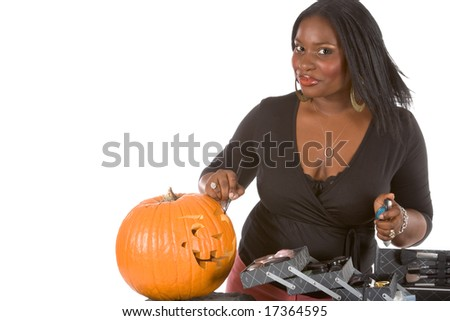African-American make up artist applying makeup on Halloween carved pumpkin (Jack O' Lantern) - stock photo