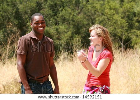 african american male and a Caucasian female enjoy a day in a park - stock photo