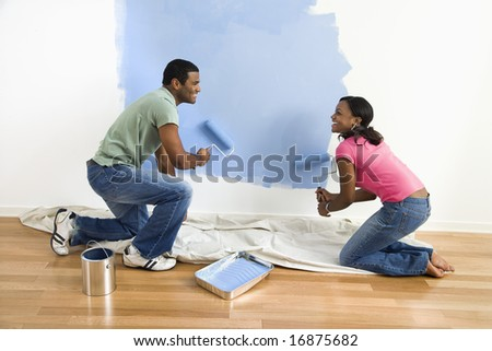 African American male and female couple painting wall blue. - stock photo