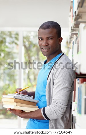 african american male college student leaning on shelf in library and looking at camera. Vertical shape, waist up, front view - stock photo