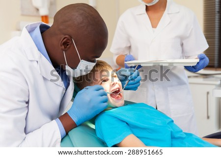 african american male dentist examining patient's teeth in dental clinic - stock photo