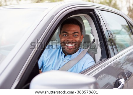 African American male driver looking to camera through car window - stock photo