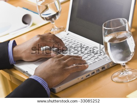 African American male hands typing on laptop keyboard. Glass of water on desk. Horizontal - stock photo
