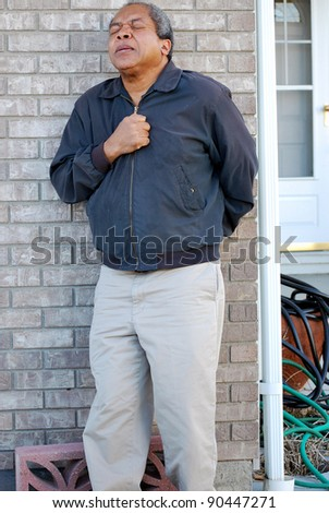 African american male having a heart attack while leaving home to go to work. - stock photo