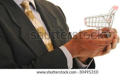 African american male holding a miniature shopping cart off to one side. Shallow depth of field. Focus on hands and shopping cart. - stock photo