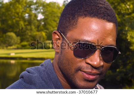 African American male in nature with sunglasses - stock photo