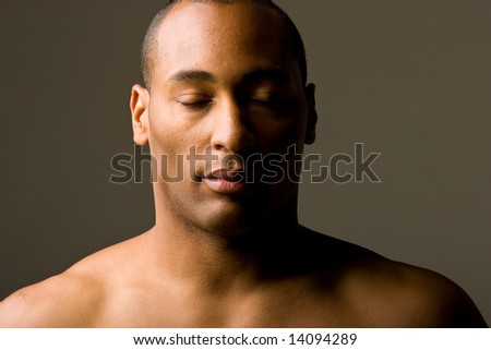 African American Male Model standing with shirt off.  Head and Shoulder Shot. Eyes Closed. Lighting is moody. - stock photo
