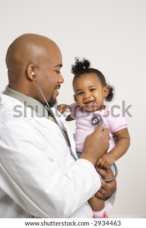 African-American male pediatrician holding and examinating baby girl with stethoscope. - stock photo
