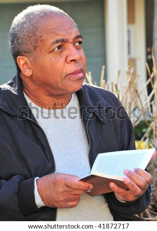 African american male reading a book outdoors.